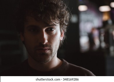 Low key closeup portrait of curly serious attractive handsome pensive young guy