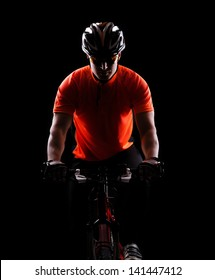 low key color silhouette of a cycling man black background