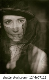 Low key dark portrait of retro style female model with black hat and veil over face. Dark film noir sexy style.