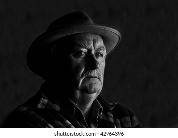 low key high contrast capture of a senior male with hat