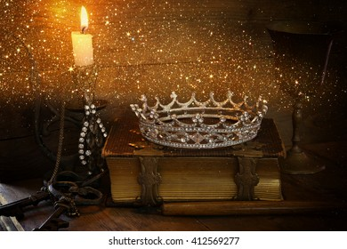low key image of beautiful diamond queen crown on old book, burning candle. vintage filtered with glitter overlay. fantasy medieval period