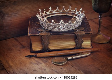 low key image of beautiful diamond queen crown on old book. vintage filtered. fantasy medieval period