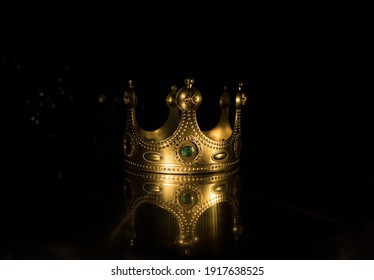 low key image of beautiful queen (or king) crown over wooden table. vintage filtered. fantasy medieval period. Selective focus. Colorful backlight