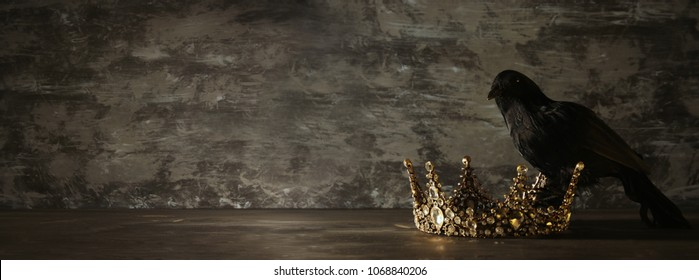 low key image of beautiful queen/king crown and black crow. fantasy medieval period. Selective focus