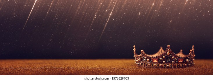 low key image of beautiful queen/king crown over gold glitter table. vintage filtered. fantasy medieval period