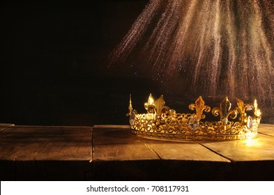 low key image of beautiful queen/king crown over wooden table. vintage filtered. fantasy medieval period