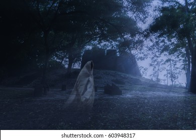 Low key image a blur white ghost in ancient forest with light and mist.