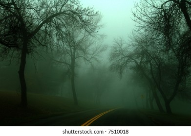 low key image of a country road on a misty and foggy morning