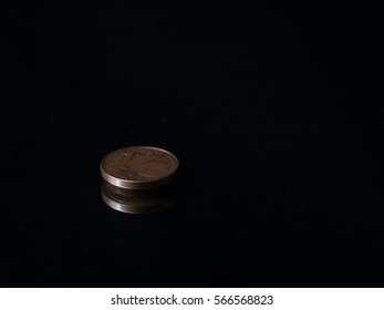 Low key image of a Euro coin on a mirrow