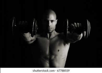 Low key image of fitness man with weights