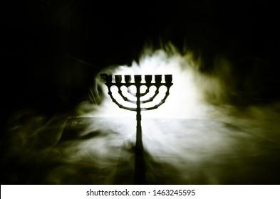 Low key image of jewish holiday Hanukkah background with menorah (traditional candelabra) on dark toned foggy background