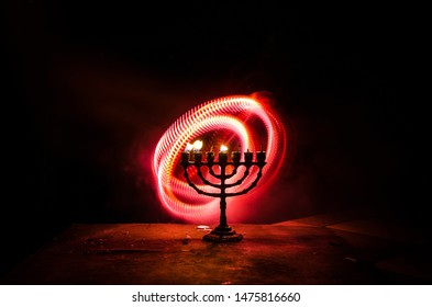 Low key image of jewish holiday Hanukkah background with menorah (traditional candelabra) on dark toned foggy background