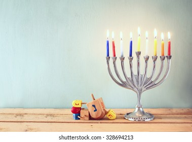 low key image of jewish holiday Hanukkah with menorah (traditional Candelabra) and wooden dreidels (spinning top)