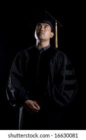 Low key image of a male model in graduation robes and regalia