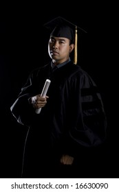 Low key image of a model in graduation robes and regalia with a diploma.