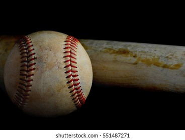Low key image of old baseball and bat showing pine tar residue on black background.