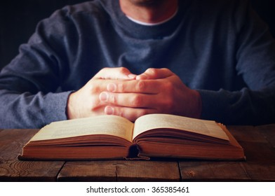low key image of person sitting next to prayer book