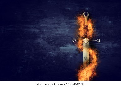 low key image of silver sword in the flames of fire. fantasy medieval period