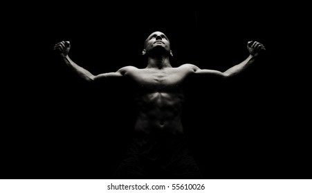 Low key image of strong male flexing