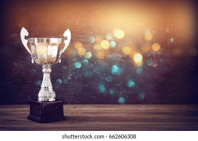 low key image of trophy over wooden table and dark background, with abstract glitter lights