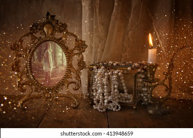 low key image of vintage frame with old photo, pearls and burning candle on wooden table. vintage filtered and toned with glitter overlay