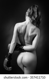 low key lighting of the back of a sexy woman wearing boxing gloves