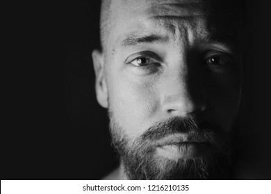 Low key lighting close-up headshot of male with beard side-lit with black background. Concerned, worried, sad expression.