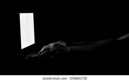 Low key male hand typing on laptop with the dark background. Concept for scammers awareness.