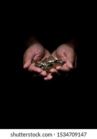 Low key photo of a brown man holding several coins in his hands.