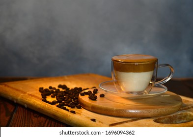 Low key photo of a cup of layered Dalgona coffee, the Korean coffee drink made of hot or cold milk topped with whipped instant coffee, sugar and hot water mixture
