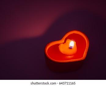 Low key photo of heart shape candle light