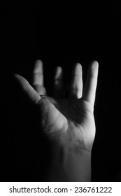 A low key photo of an open hand with upstretched fingers.