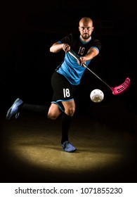 Low key photography of a shooting floorball player.