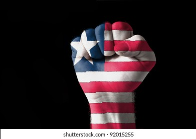 Low key picture of a fist painted in colors of liberia flag