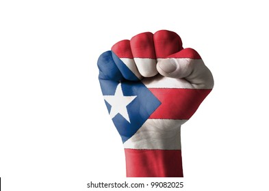 Low key picture of a fist painted in colors of puertorico flag