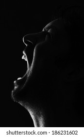 low key picture showing the silhouette of a man shouting in anger