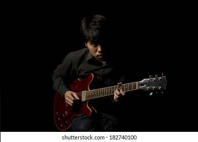 low key portrait of asian young musician playing guitar