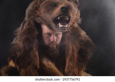 Low key portrait of a bearded war shaman in bearskin with an ancient ax in his hands. High quality cosplay of the ancient werewolf war