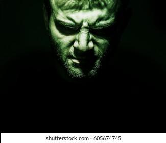 Low key portrait of evil, devil, bad, angry face of man on a black background, dark side human soul, crazy