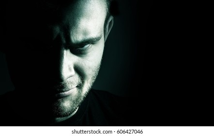 Low key portrait of evil, devil, bad, angry face of man on a black background, dark side human soul, crazy,