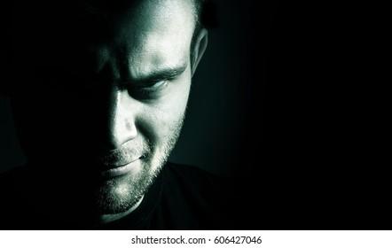 Low key portrait of evil, devil, bad, angry face of man on a black background, dark side human soul, crazy,