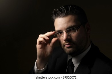 Low key portrait of handsome man with glasses