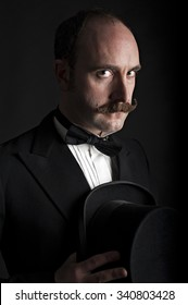 Low key portrait of man holding his top hat chest level. He has a curled moustache and can be described as either English, gentleman, magician, or fancy dress.