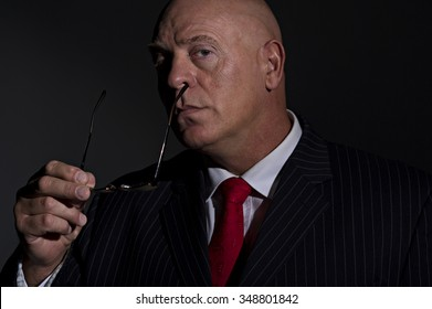 Low key portrait of a mature male wearing a pin stripe suit. He is removing his glasses. He resembles a criminal boss, or no nonsense CEO
