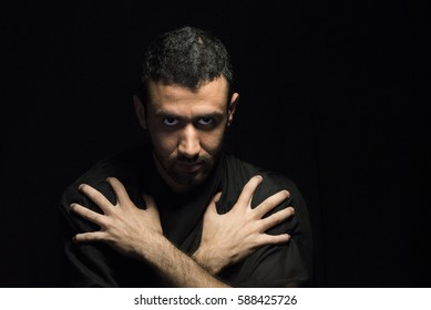 Low Key Portrait of Middle Eastern Man with his Hands on His Shoulders.