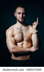 Low key portrait of muscular shirtless man at dark background standing looking at camera, pointing up