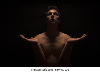 Low key portrait of shirtless man in Yoga position. Black background