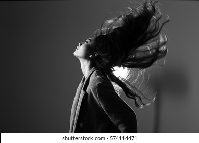 low key portrait of slim healthy woman with fog and light from back, sexy pose s curve and shadow, black and white concept, copy space motion movement blur fluttering hair