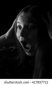 A low key portrait of a teenage girl screaming. Illuminated by just one light. It could be a TV, computer, or any light source to create a dramatic horror scene. Black and white for a thrilling photo.
