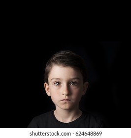 Low key portrait of young boy isolated on black background. Plenty of space left for copy. for Flyers, posters and other commercial purposes. Serious face